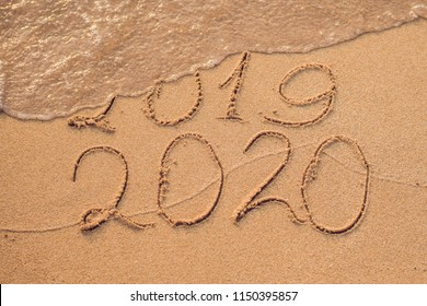 New Year 2020 is coming concept - inscription 2019 and 2020 a beach sand, the wave is almost covering the digits 2019
