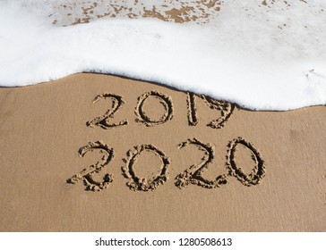 New Year 2020 is coming concept - inscription 2019 and 2020 on a beach sand, the wave is starting to cover the digits 2019.