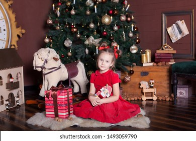 New Year 2020. Merry Christmas, happy holidays. Little girl in a red dress holds a vintage wooden nutcracker toy near a classic Christmas tree at home. Ballerina with the Nutcracker on New Year's Eve.