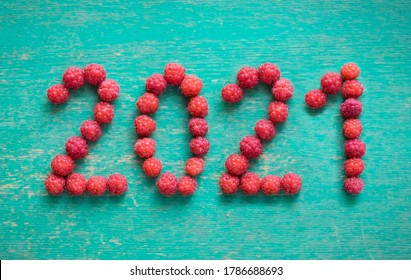 new year 2021 made of berries on blue wooden background