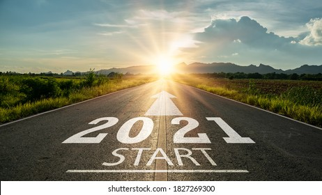 New year 2021 or start straight concept.word 2021 written on the road in the middle of asphalt road at sunset.Concept of planning and challenge or career path,business strategy,opportunity and change - Shutterstock ID 1827269300