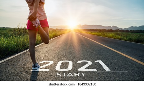 New year 2021 or start straight concept.word 2021 written on the asphalt road and athlete woman runner stretching leg preparing for new year at sunset.Concept of challenge or career path and change.