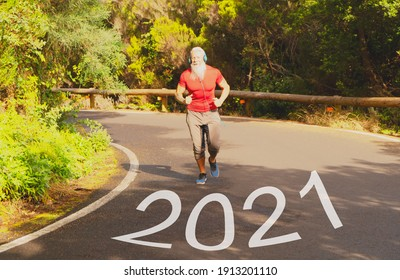 New year 2021 or start straight concept, word 2021 written on the asphalt road and athlete man running for new year. Concept of challenge or career path and change.