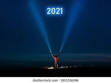 New year 2021. Success new year concept. Milky Way.Long exposure photography, a man holding a flashlight and illuminating the sky full of stars with 2021 inscription.