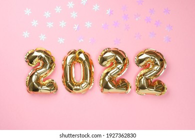 New Year 2022. Foil balloons numbers 2022 on a pink background. New Year Christmas.