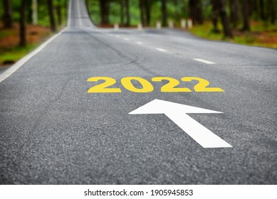 New year 2022 on asphalt road surface with white arrow. Business beginning concept and keep moving forward idea