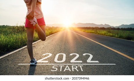 New year 2022 or start straight concept.word 2022 written on the asphalt road and athlete woman runner stretching leg preparing for new year at sunset.Concept of challenge or career path and change. - Shutterstock ID 2037394946
