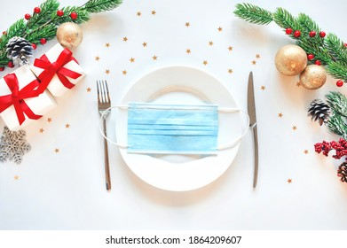 new year background 2021. holiday in quarantine. A medical mask lies on a plate decorated for Christmas. Quarantine New Year's table setting attributes