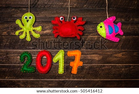 new year background with christmas handmade toys made of felt on dark rustic wooden background