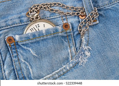 New Year background. Vintage pocket watch with silver chain  in destroyed ripped torn denim blue jeans pocket,  New Year clock on fashion denim background.