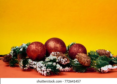 New Year balls and a branch of a Christmas tree in warm tones