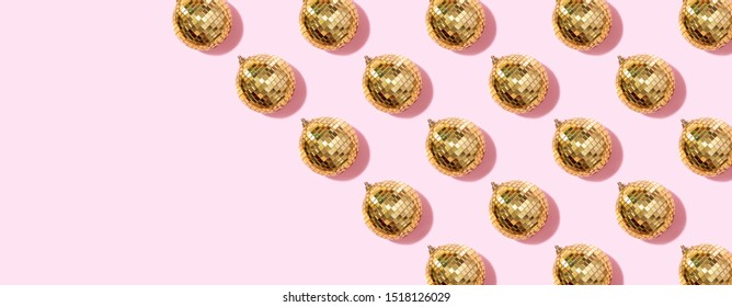 New year baubles. Shiny gold disco balls on pink background. Pop disco style attributes, retro concept. Creative Christmas pattern. Flat lay, top view