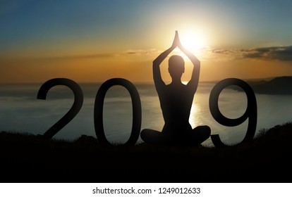 New year and new beginnings concept. Silhouette of person meditating in lotus pose as part of 2019 number on sunrise