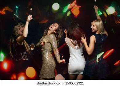 New Year, birthday, 8 march dance party. Happy friends company with drinks, Christmas celebration, modern youth life. Women enjoying night out at bar dancing in disco lights.
