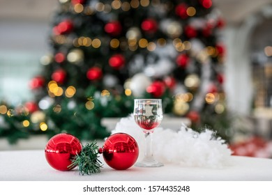 New Year, with Bokeh effect in the background Christmas Pine Tree and lights, champagne glass and Christmas Ornaments in the foreground