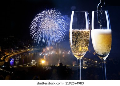new year in Budapest - two glasses of champagne against fireworks over Budapest Parliament, the Danube and chain bridge