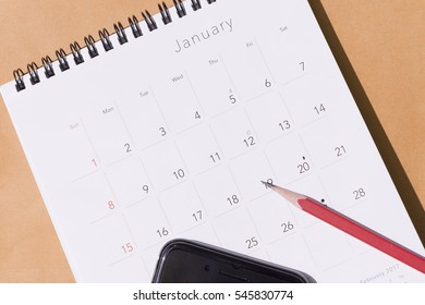 The  new year calendar  on the brown paper background with the red pencil and mobile phone