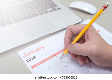 new year calendar, pencil writing, laptop and man's hand