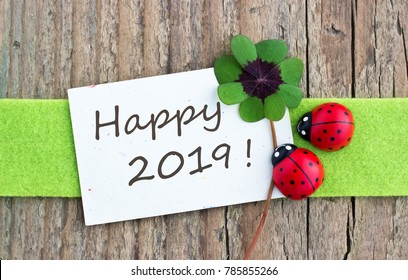 New Year card with leafed clover and ladybugs on wooden background