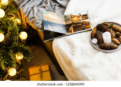 New Year celebrating. Photobook with photos of summer travel under the Christmas tree