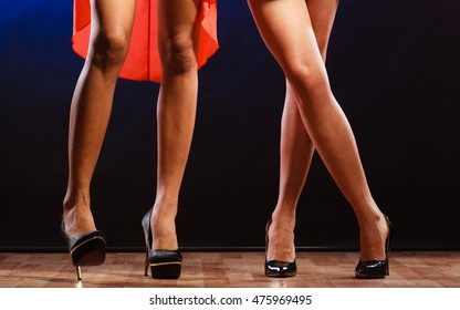 New year, celebration, disco concept - women in evening dresses dancing in club, part of body female legs in high heels on party floor
