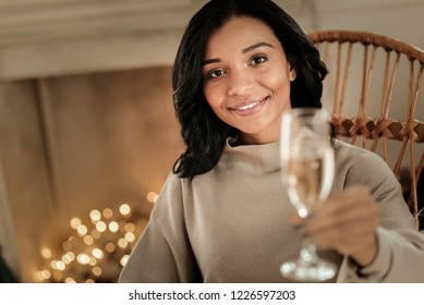 New Year celebration. Happy beautiful pleasant woman smiling and looking at you while cheering with champagne