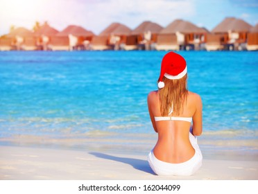 New Year celebration on Maldives, travel on winter holidays to summer destinations, back side, wearing red Santa Claus hat