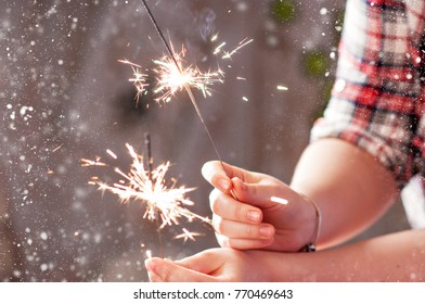 New Year and Christmas 2018. Christmas lights in the hands of the child. Magic and holiday.