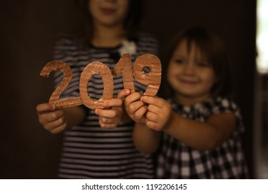 New Year and Christmas 2019, children are holding paper figures on a dark background