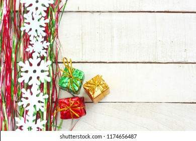 New Year, Christmas background, green and red tinsel, garland snowflakes, three gift boxes on white wooden table