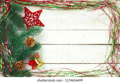 New Year Christmas background, sparkles tinsel, red carved star, decoration bell on white wooden table, space for text