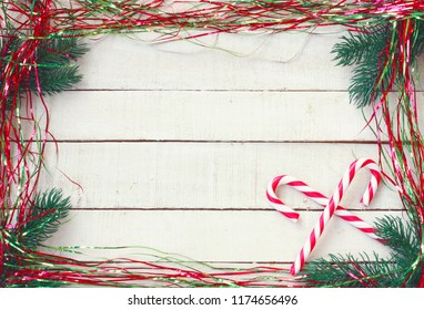 New Year, Christmas background, tinsel, candy striped, branches of fir-tree on white wooden table