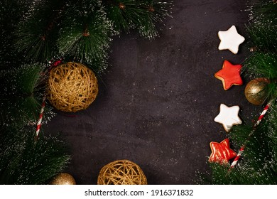 New Year and Christmas background, Christmas tree branches and toys, gift boxes, gingerbread, on a black textured background, free space for design top view