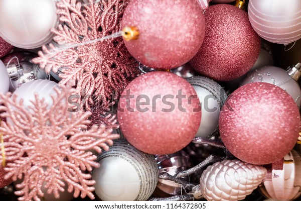new year and christmas balls background. mix of rose gold and silver toys baubles snowflakes and pines. festive decoration