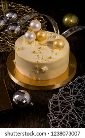 New Year or Christmas cake with peaches and mascarpone cream, decorated with chocolate balls on wooden table
