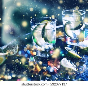 New Year , Christmas. Closeup vodka in a glass with ice, lime vodka, Gin, tonic, tequila. Holiday decoration. Multicolored lights, gold tinsel, sparkling snow.