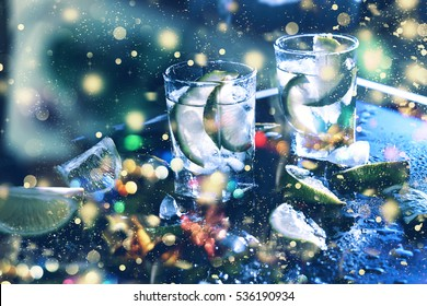 New Year Christmas. Closeup vodka in a glass with ice, lime vodka, Gin, tonic, tequila. Holiday decoration. Multicolored lights, gold tinsel, sparkling snow.