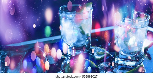 New Year, Christmas. Closeup vodka in a glass with ice, lime, vodka, Gin, tonic, tequila. Holiday decoration. Multicolored lights, gold tinsel, sparkling snow. Multicolored sequins. Falling snowflakes