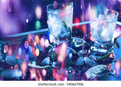 New Year, Christmas. Closeup vodka in a glass with ice, lime, vodka, Gin, tonic, tequila. Holiday decoration. Multicolored lights, gold tinsel, sparkling snow, Multicolored sequins. Falling snowflakes