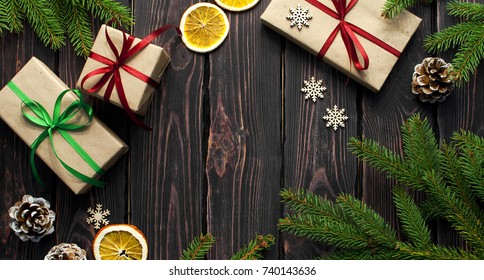 New Year Christmas composition Fir branch Pine cone New Year's gift Orange Snowflakes Snow Decorative ribbon. Traditional festive decoration christmas dark background top view. Long format.