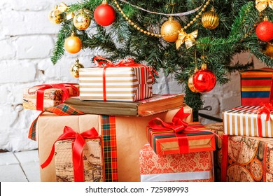 New Year and Christmas composition with packed gifts and fir branch at white brick wall background.