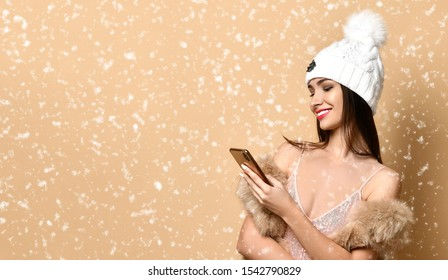 New Year and Christmas concept. Glad and awing rich girl in shimmering evening gown, fur, winter hat is looking at her cell phone under the snow and smiles on beige with copy space