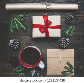 New Year or Christmas concept, wrapping paper, cup of coffee, fir branches, cones, gift, on wooden background flat lay