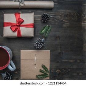 New Year or Christmas concept, wrapping paper, cup of coffee, fir branches, cones, gift, place for text on a wooden background flat lay