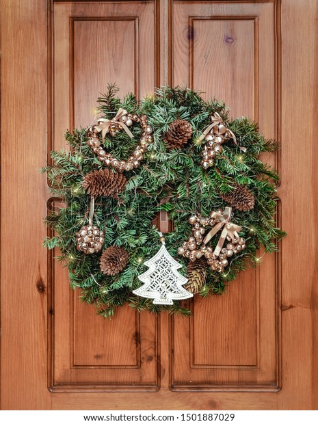 New Year and Christmas decor. Ornament a wreath from branches ate with cones, lights of a garland and gold spheres. Traditional Christmas decoration for interior and exterior.