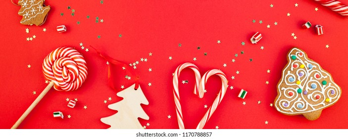 New Year or Christmas decoration flat lay top view Xmas holiday celebration handmade decor wooden toys sweets golden stars glitter on red paper background. Template frame long wide banner