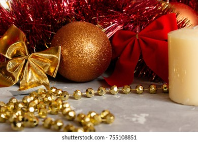 New year (Christmas) decoration on gray table. Golden and red balls, candle, bow-knots, tinsel and cone. Cozy holiday mood.
