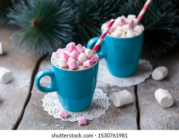 New Year, Christmas drink. Two mugs of hot chocolate with colorful marshmallows on wooden background. Winter time. Holiday concept.