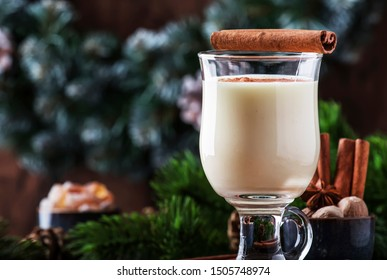 New Year or Christmas Eggnog cocktail - hot winter or autumn drink with milk, eggs and dark rum, sprinkled with cinnamon and nutmeg in a glass on wooden background, festive decoration