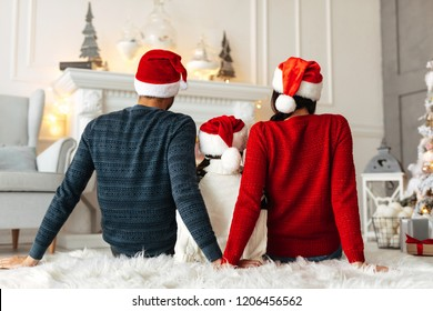 New Year. Christmas. Family. Back view of young parents and their little daughter in Santa hats spending time together at home